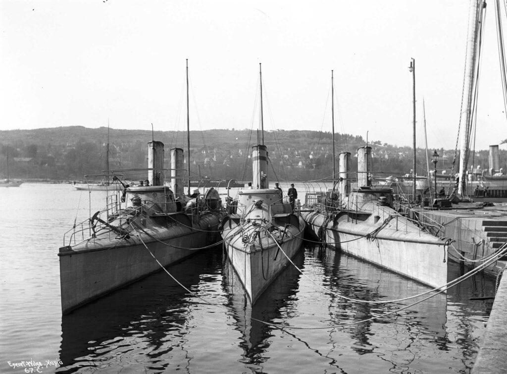 Norska torpedbåtar från 1900 vid hamn.